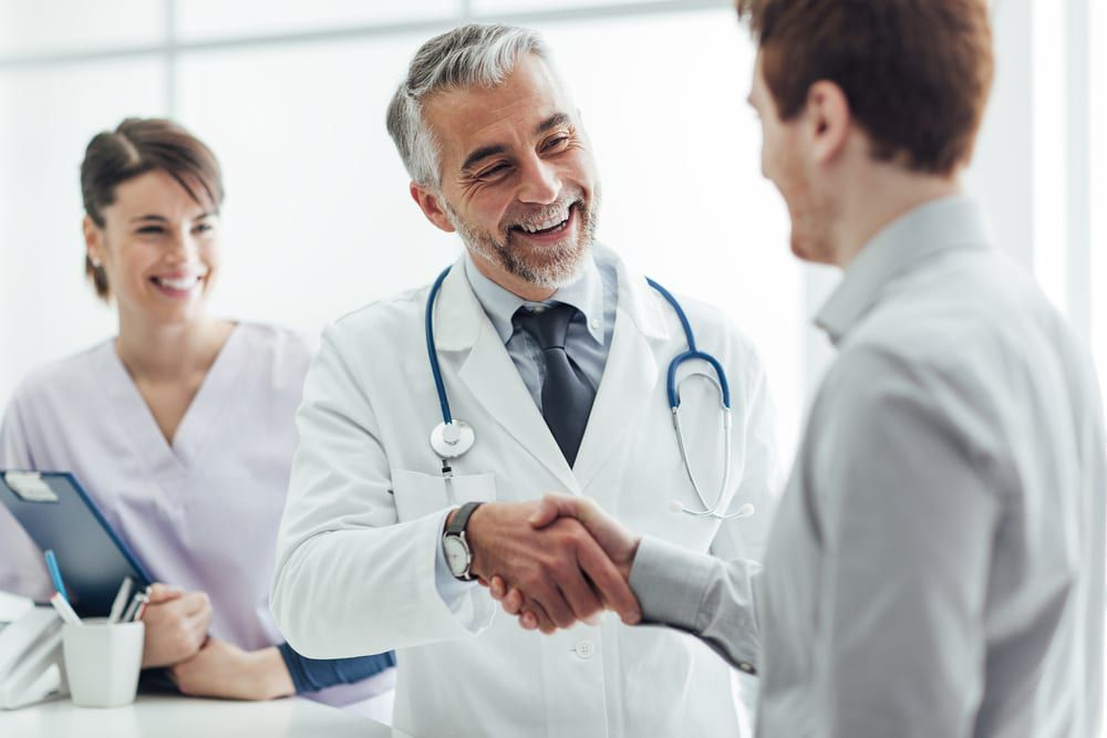 doctor at the clinic giving an handshake to his patient